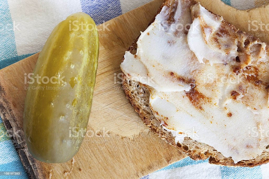 Slice of bread with lard and pickled cucumber stock photo