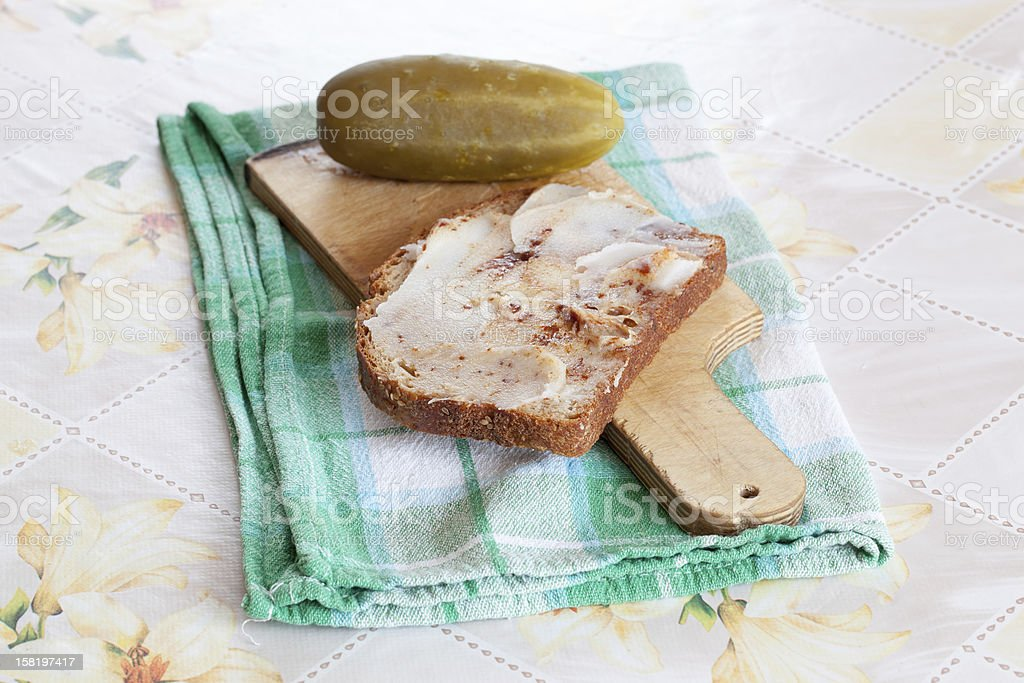 Slice of bread with lard and pickled cucumber Slice of bread with lard and pickled cucumber laying on the cutting board Bread Stock Photo
