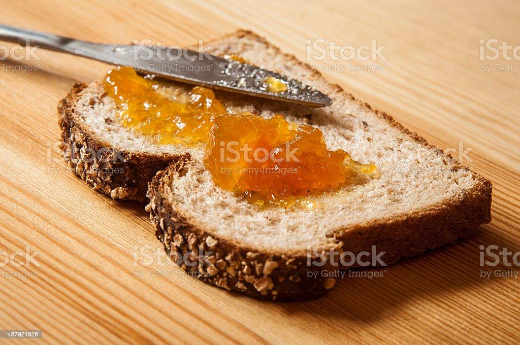 Slice of bread with orange jam stock photo