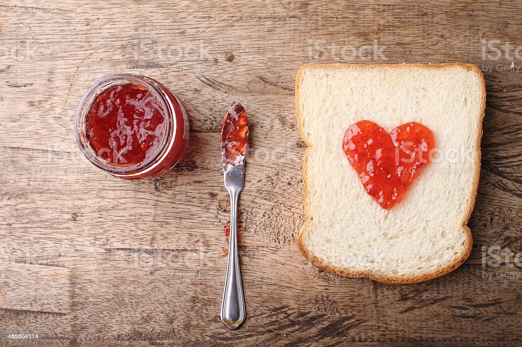 slice of bread with strawberry jam in heart shape stock photo