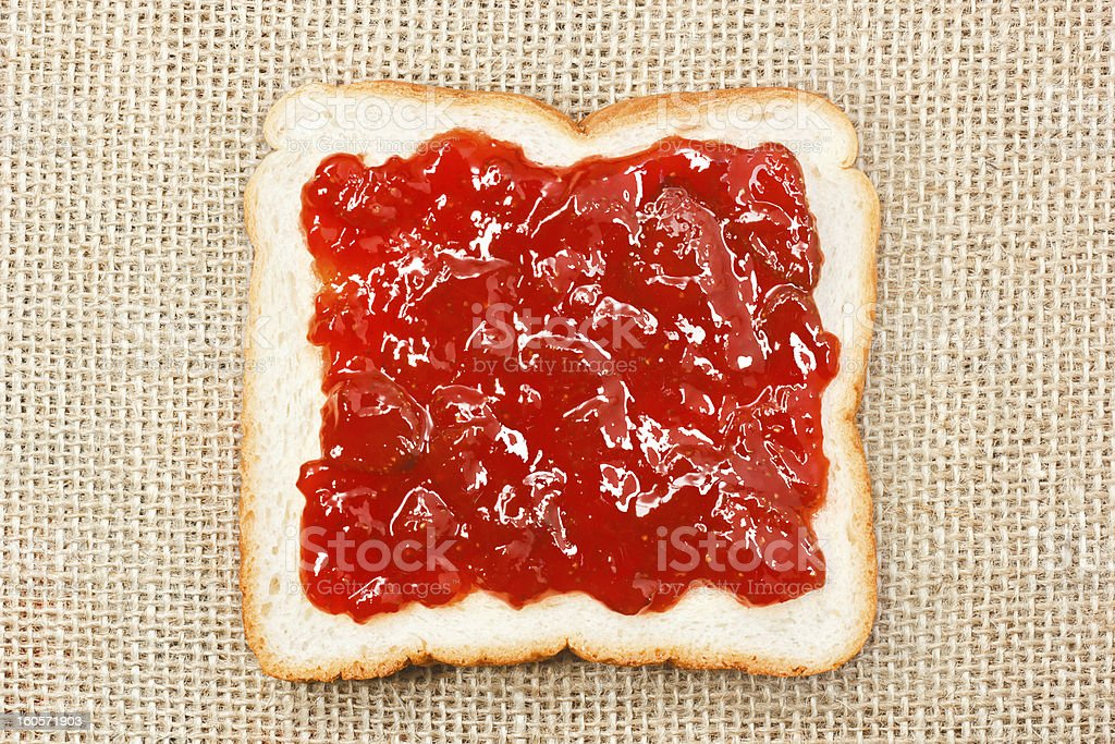 slice of bread with strawberry jam on sacking background royalty-free stock photo