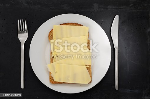 Slice of brown bread with cheese on a white plate, stainless steel silverware and black stone background.