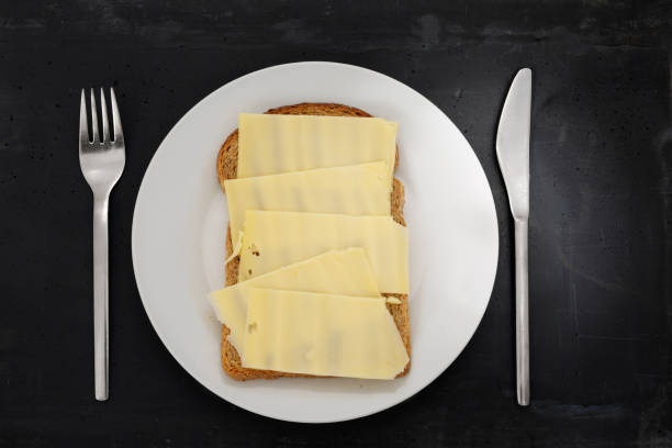 Slice of brown bread with cheese on a white plate. stock photo