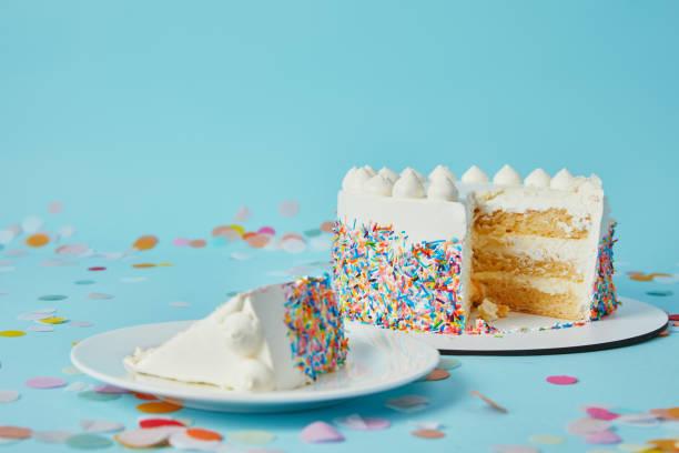 slice of cake with cut cake on blue background with confetti - кусок торта стоковые фото и изображения