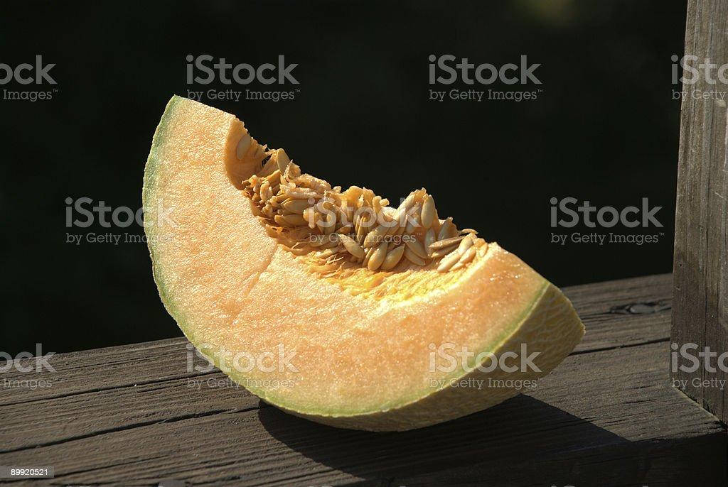 Slice of cantaloupe against dark background stock photo