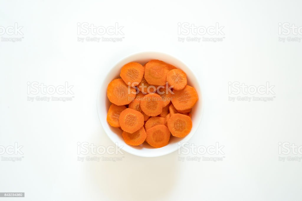 Slice of carrots in white dish on white color background stock photo