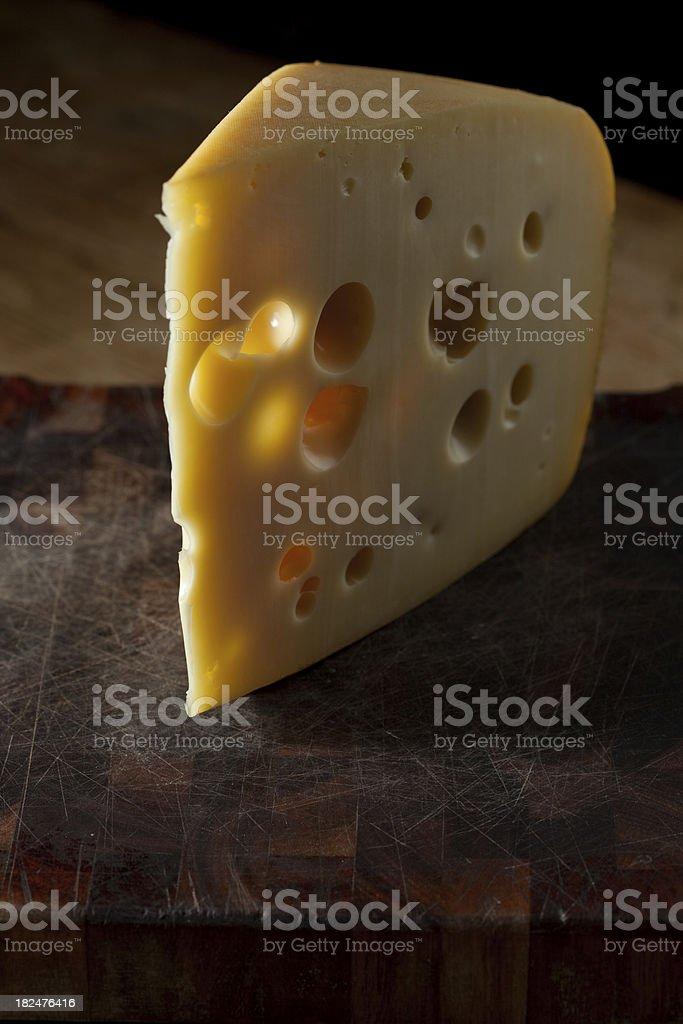 Slice of cheese with holes royalty-free stock photo