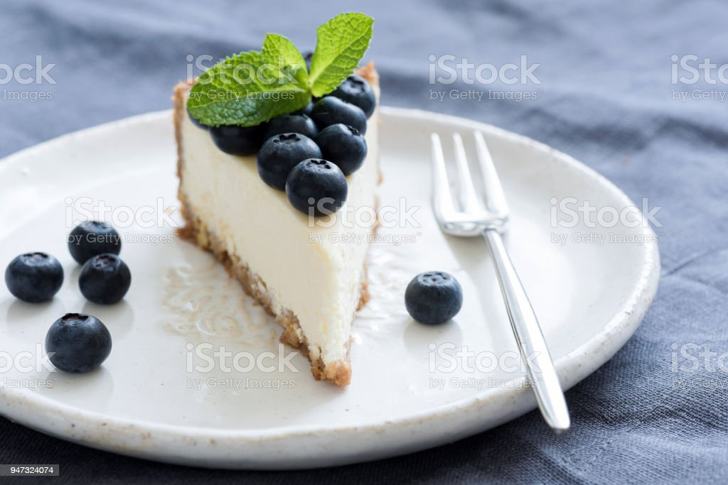 Slice of cheesecake with fresh blueberries and mint leaf on white plate stock photo