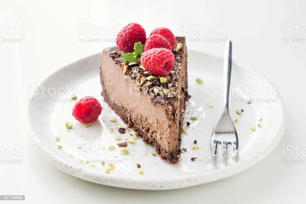 Slice of chocolate cake cheesecake decorated with crushed pistachio nuts, raspberries and mint leaf stock photo