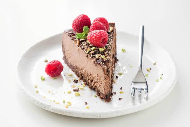 stück schokolade kuchen käsekuchen mit zerkleinerten pistazien, himbeeren und minze dekoriert - schokoladen käsekuchen törtchen stock-fotos und bilder