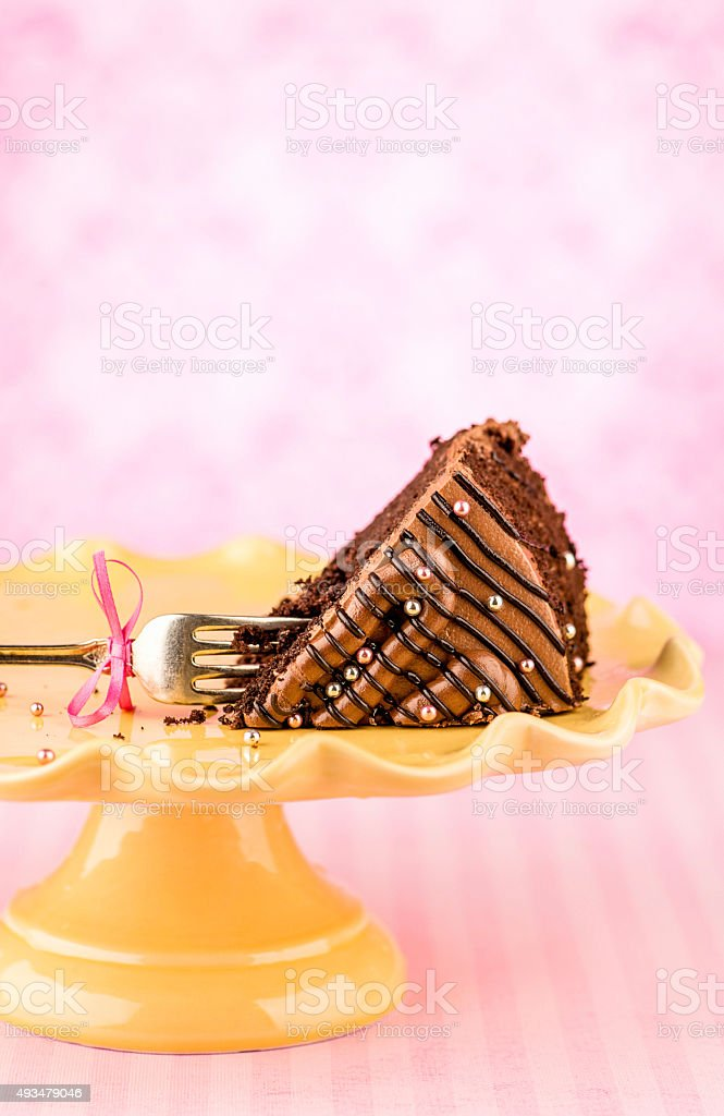 Slice of chocolate cake on a cake stand with fork stock photo