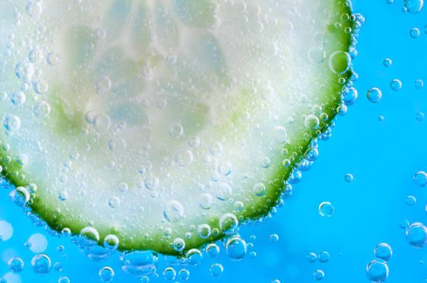 gurkenscheibe in sodawasser - gurke gesund stock-fotos und bilder