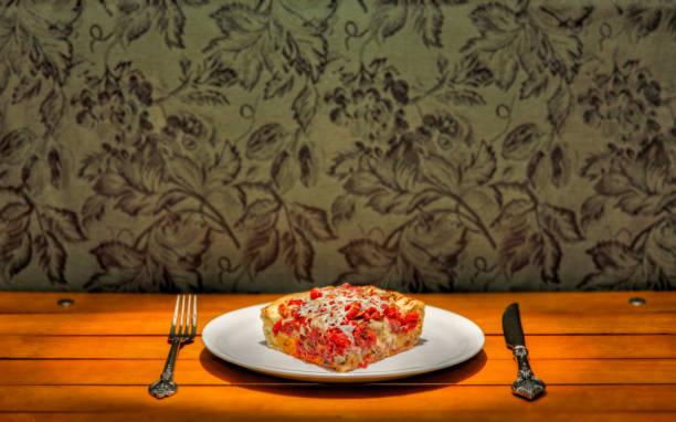 een plak van pizza van de diepe schotel op een plaat met een spotlight op het en een mes en vork - dikke pizza close up stockfoto's en -beelden
