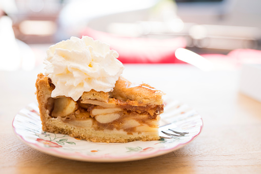 slice of Dutch apple pie with whipped cream on saucer, table, against blur background