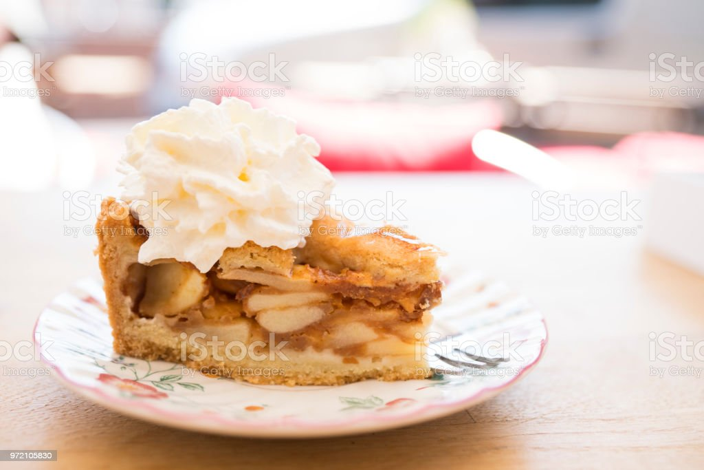 slice of Dutch apple pie with whipped cream on saucer, table, against blur background stock photo