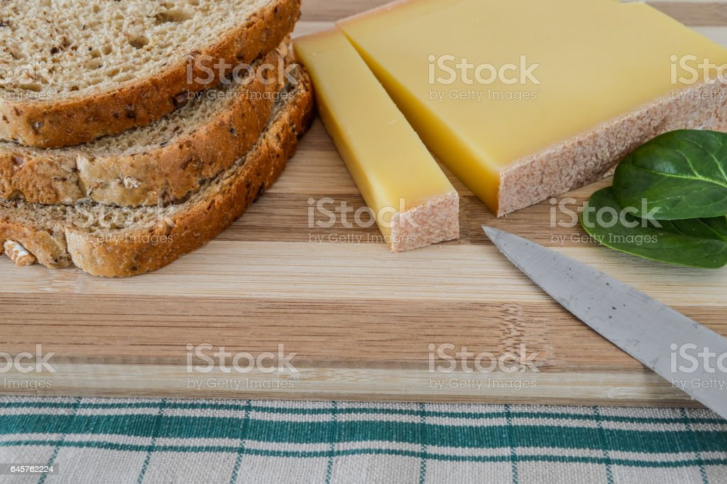 slice of french comte cheese on wood cutting board with fresh green spinach leaves and sliced 7-grain bread stock photo