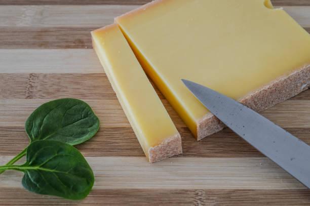 slice of french comte cheese on wood cutting board with green spinach leaves - ser comte zdjęcia i obrazy z banku zdjęć