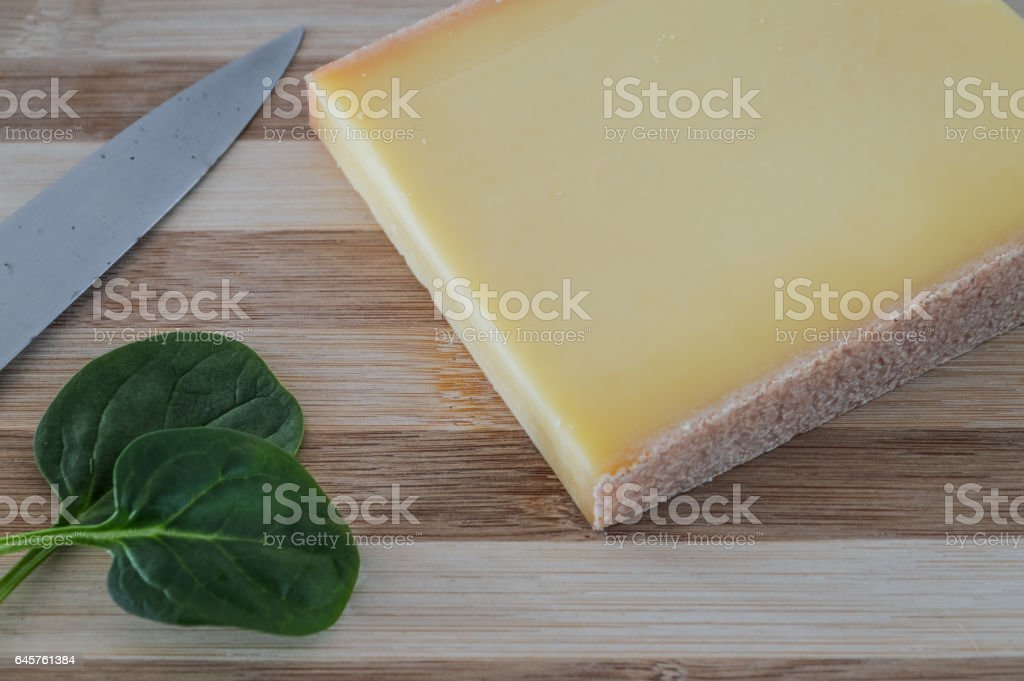 slice of french comte cheese on wood cutting board with green spinach leaves stock photo