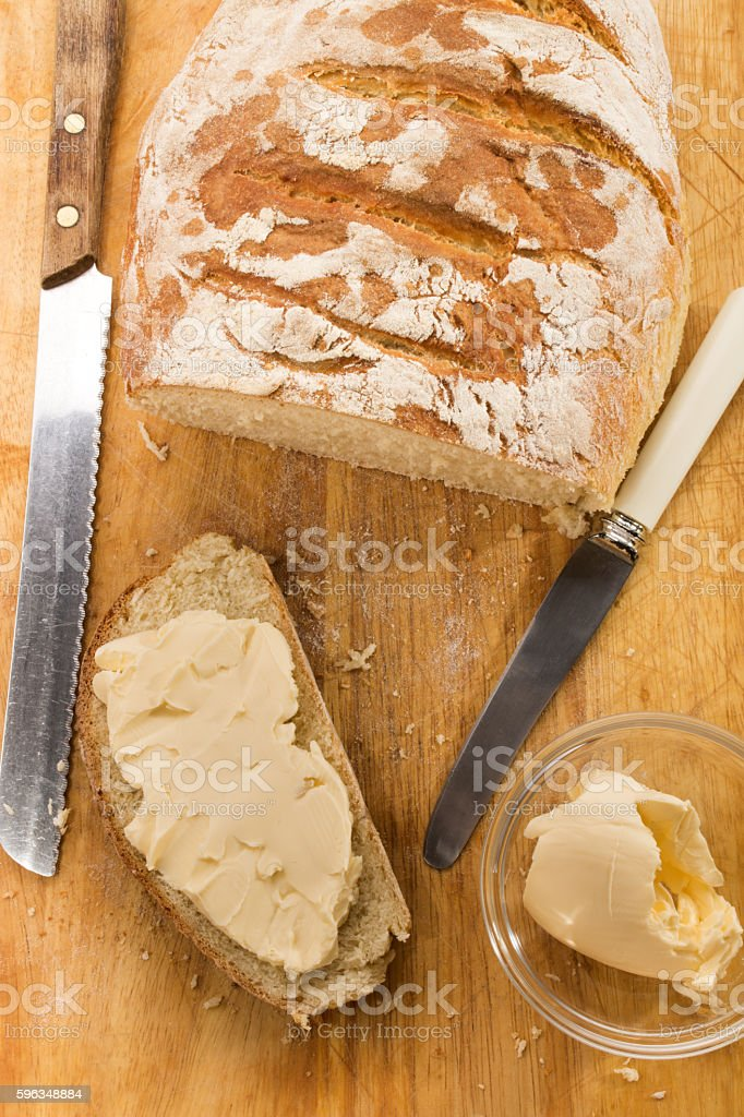 slice of freshly baked floured country bread with butter royalty-free stock photo