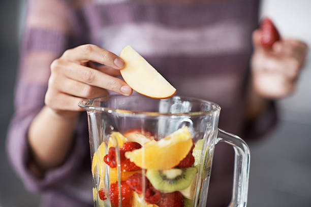 Slice of heaven A closeup cropped shot of a woman's hand putting sliced fruits into a blender blender stock pictures, royalty-free photos & images
