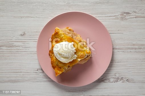Slice of homemade apple pie with ice cream on a pink plate over white wooden surface, overhead view.