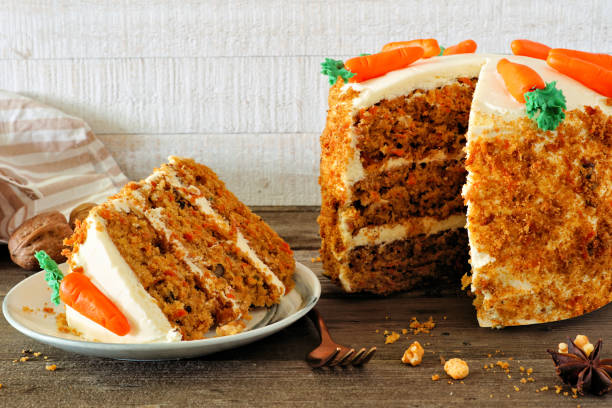 Slice of homemade carrot cake with cream cheese frosting, side view table scene against white wood stock photo