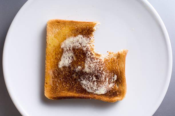 slice of hot buttered toast with a bite taken out - tallrik uppätet bildbanksfoton och bilder