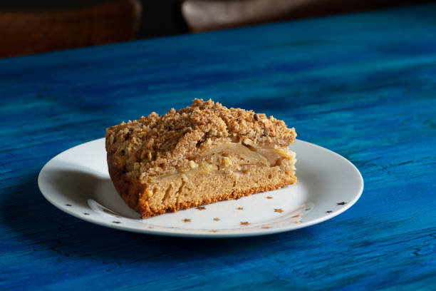 Slice of Irish Apple Cinnamon Streusel Coffee Cake on Star Plate on Blue Table stock photo