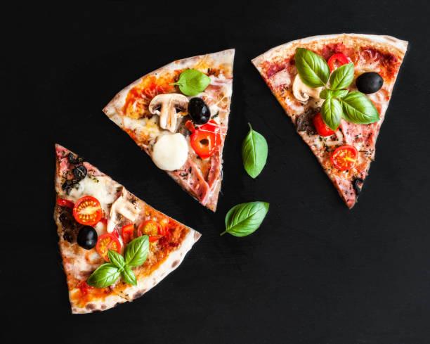 slice der italienischen klassischen pizza mit salami, schinken und speck, käse, pfeffer und oliven über schwarze tafel hintergrund - fladenbrotpizza stock-fotos und bilder