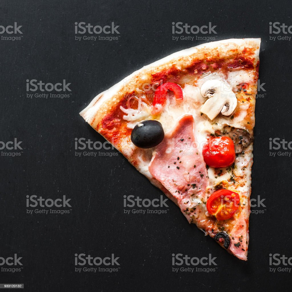 Slice of  Italian classic Pizza with salami, ham and bacon,  cheese, pepper and olives over  black  background with copy space stock photo