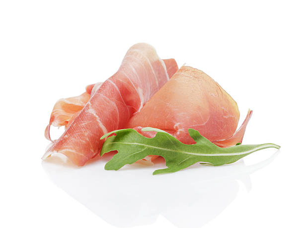 slice of italian prosciutto with arugula leaf stock photo