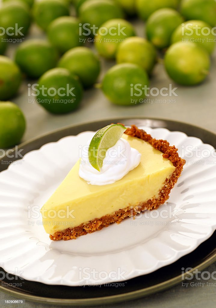 A slice of key lime pie surrounded by a pile of green limes stock photo