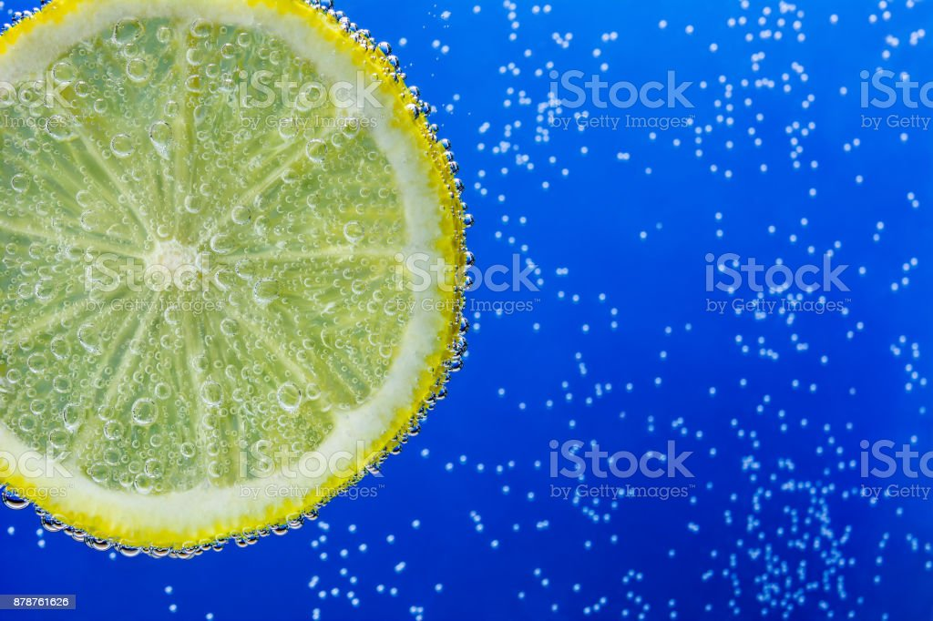 slice of lemon in the blue water with bubbles stock photo