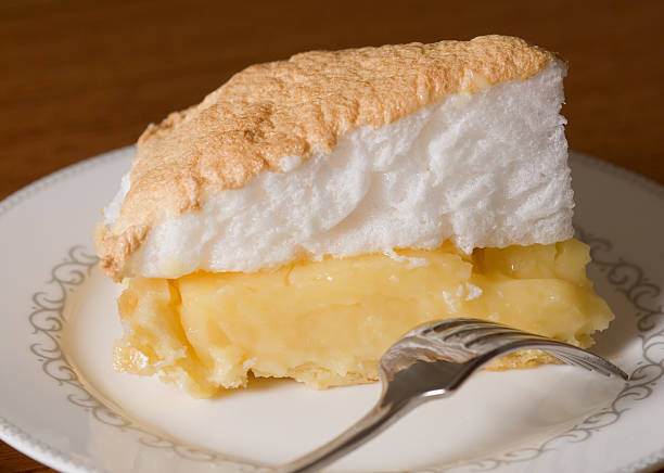 Slice of lemon meringue pie on a kitchen table stock photo
