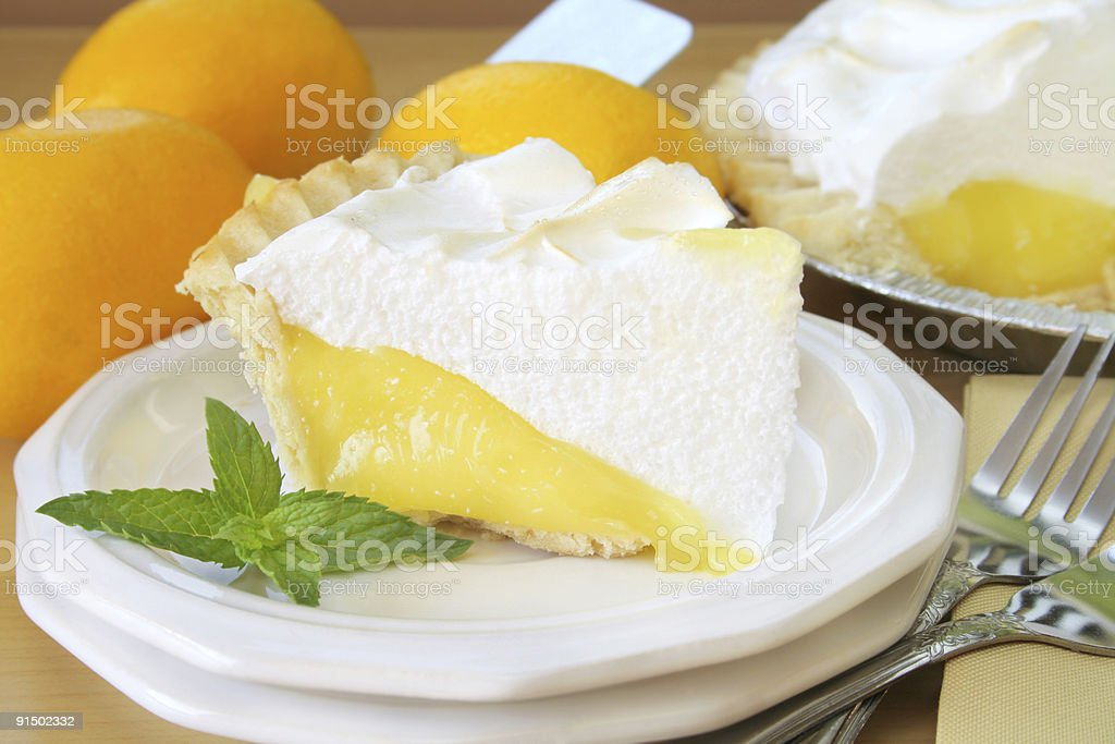 Slice of lemon meringue pie on plate with forks stock photo