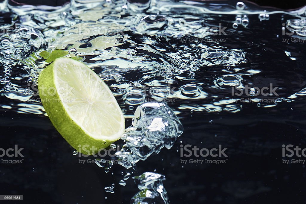 Slice of lime (lemon)  falling in water near the surface royalty-free stock photo