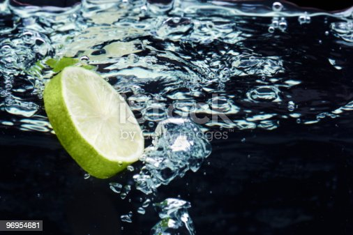 134949478 istock photo Slice of lime (lemon)  falling in water near the surface 96954681