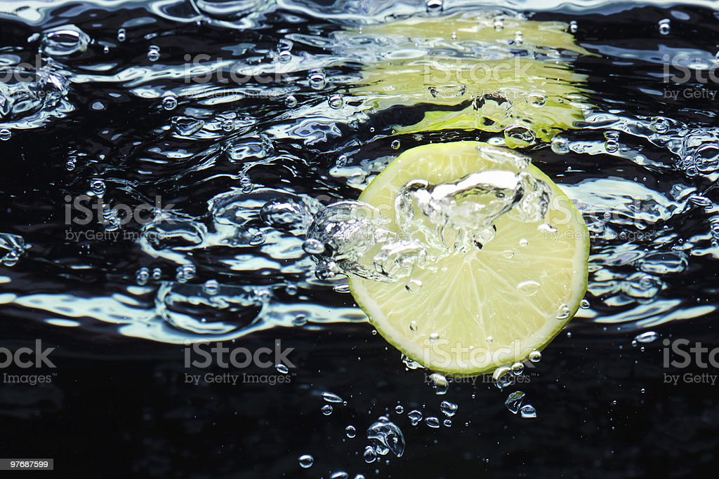Slice of lime  falling in water with air bubbles royalty-free stock photo