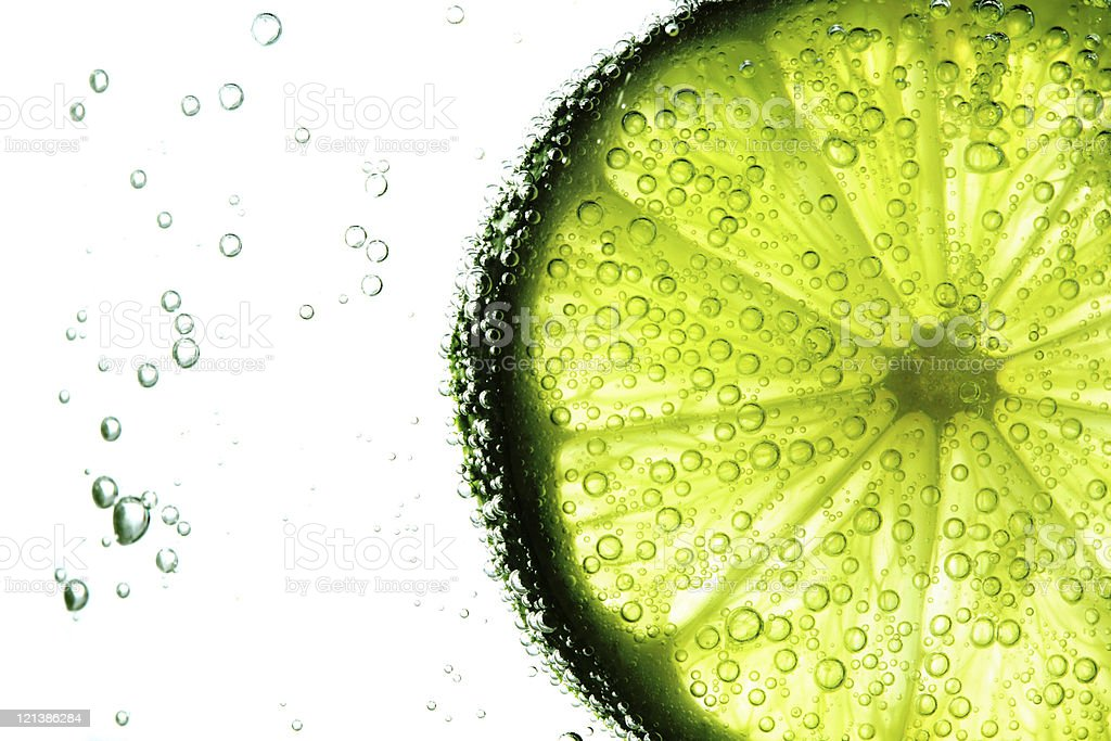 A slice of lime in water with bubbles all around stock photo
