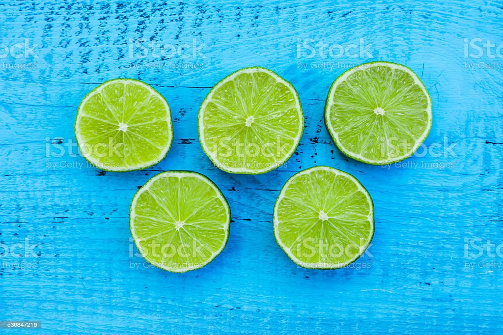 Slice of limes on the rustic blue background stock photo