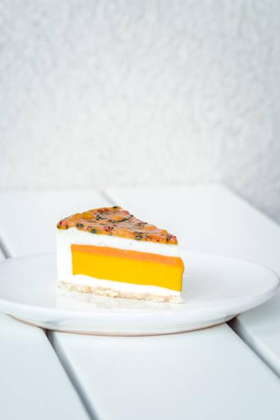 stück mango maracuja-kokos-kuchen auf weiß - paleo kuchen stock-fotos und bilder