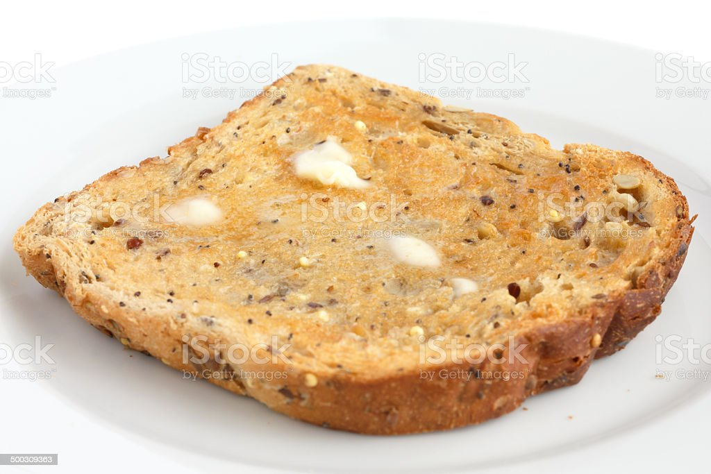 Slice of multi-seed wholegrain bread toasted and buttered stock photo