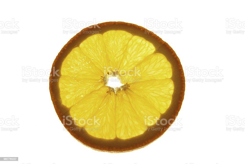 Slice of orange in back lite royalty-free stock photo