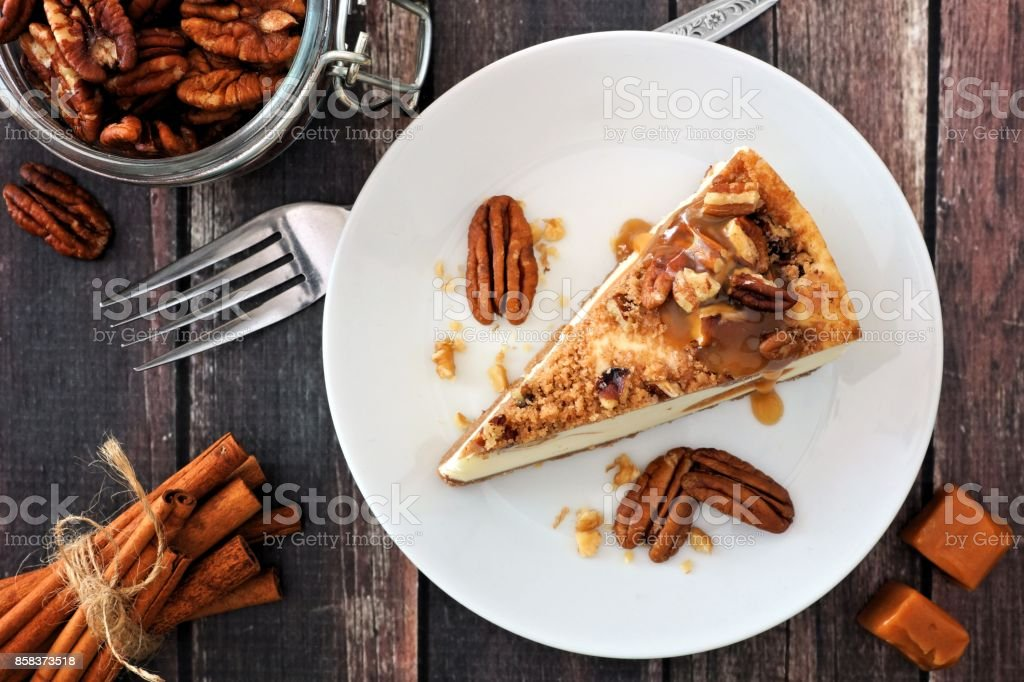Slice of pecan caramel cheesecake, top view over wood royalty-free stock photo