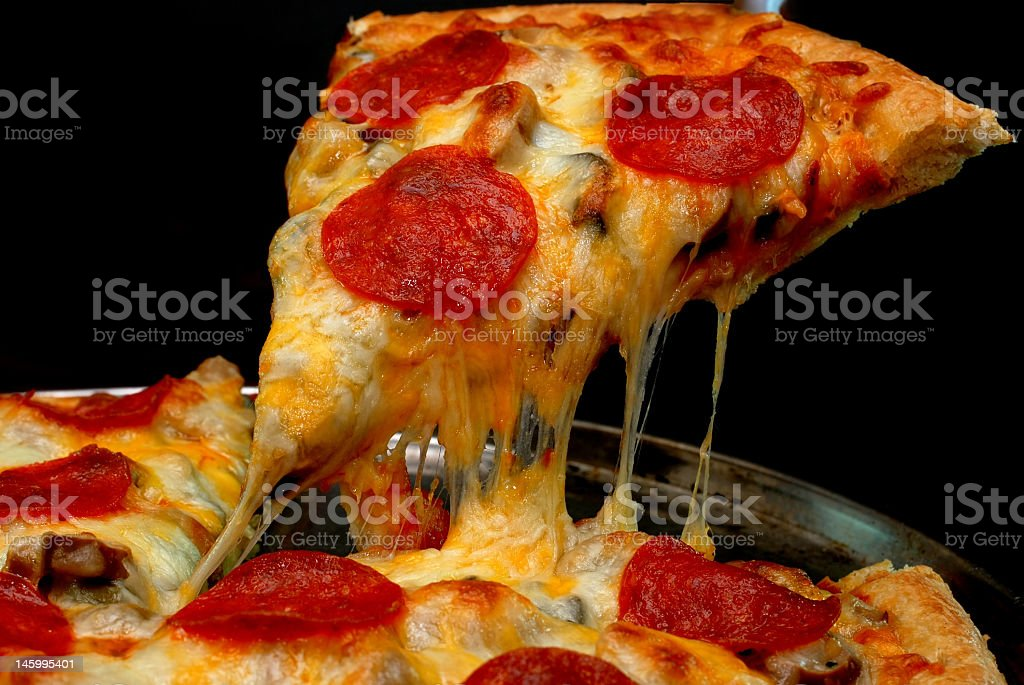 Slice of pepperoni pizza with pulling cheese stock photo