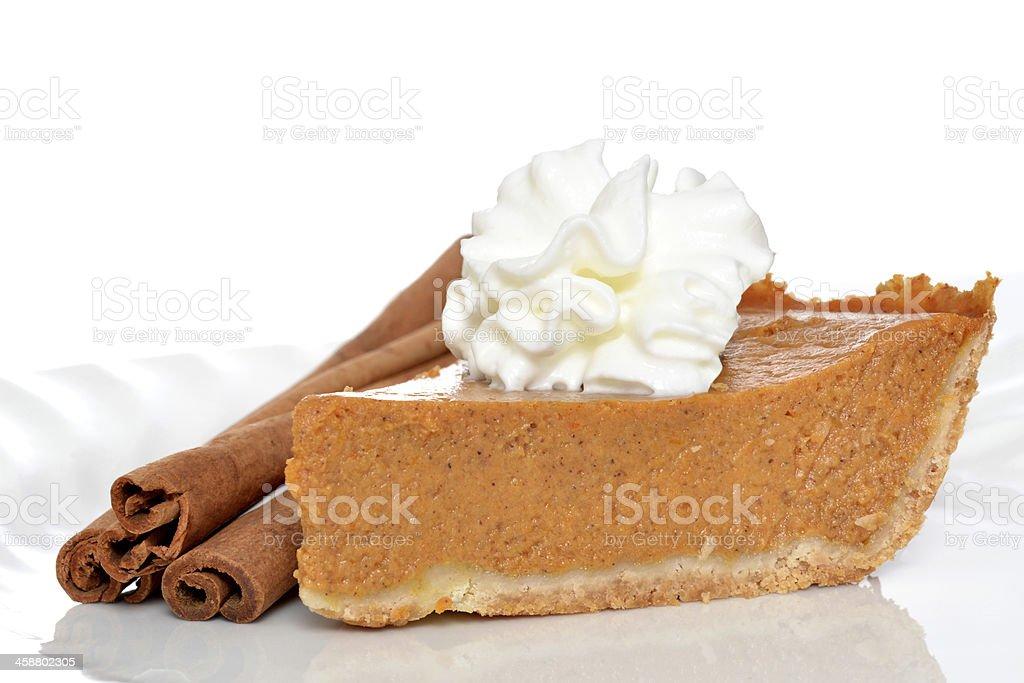 A slice of pie with three decorative cinnamon sticks stock photo