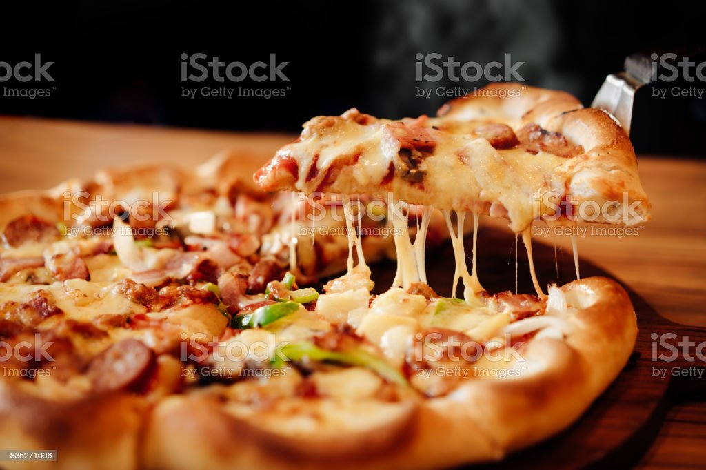 Slice of pizza cheese crust seafood topping sauce. with bell pepper vegetables delicious tasty fast food italian traditional and soft drink carbonated fresh on wooden board table classic in side view stock photo
