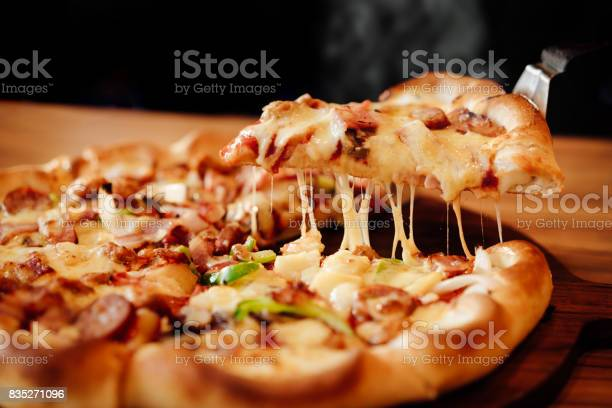 Slice of pizza cheese crust seafood topping sauce. with bell pepper vegetables delicious tasty fast food italian traditional and soft drink carbonated fresh on wooden board table classic in side view