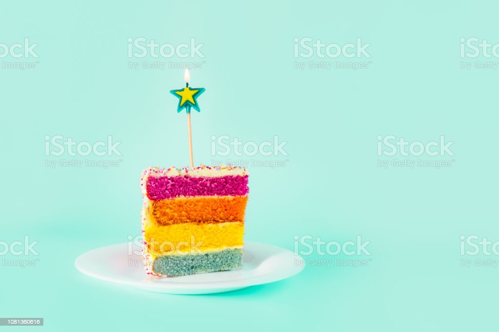 Slice of Rainbow cake with birning candle in the shape of star on white round plate isolated on turquoise background. Happy bithday, party concept. Selective focus. Copy space. stock photo