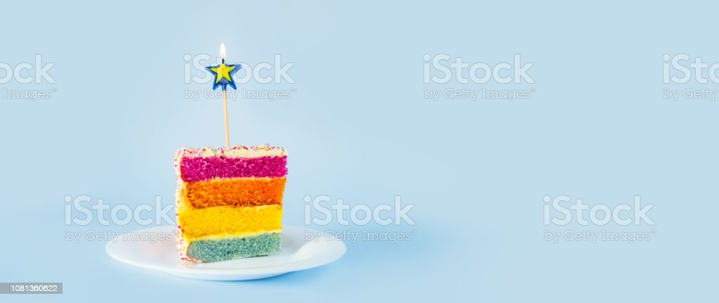 Slice of Rainbow cake with birning candle in the shape of star on white round plate isolated on blue background. Happy bithday, party concept. Wide banner. Selective focus. Copy space. stock photo